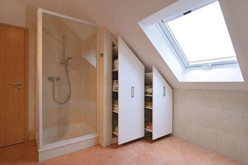 Weißer Einbauschrank im Badezimmer unter der Dachschräge mit großen Auszügen