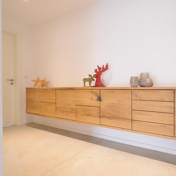 Das Sideboard aus Holz in der Garderobe für viel Stauraum