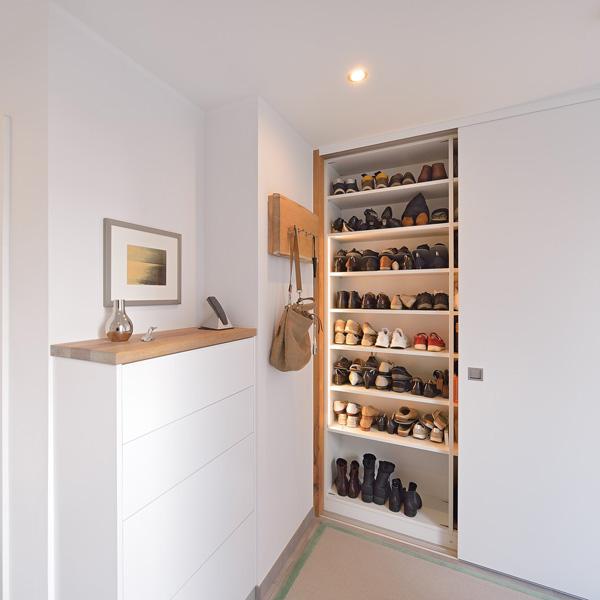Garderobe mit Telefonschrank und Schuhschrank, der hinter weißen Schiebetüren verschwindet.