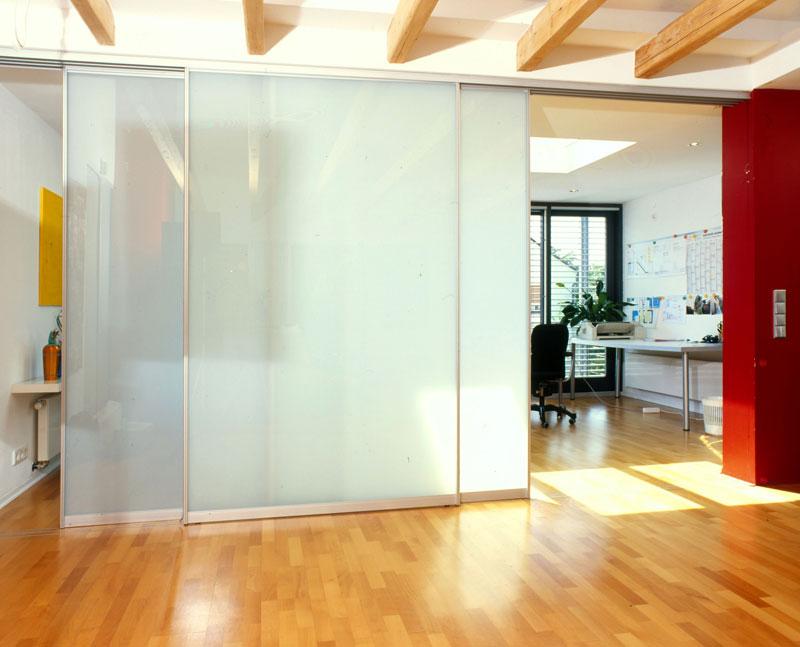Raumhohe Ganzglasschiebetüre als Raumteiler