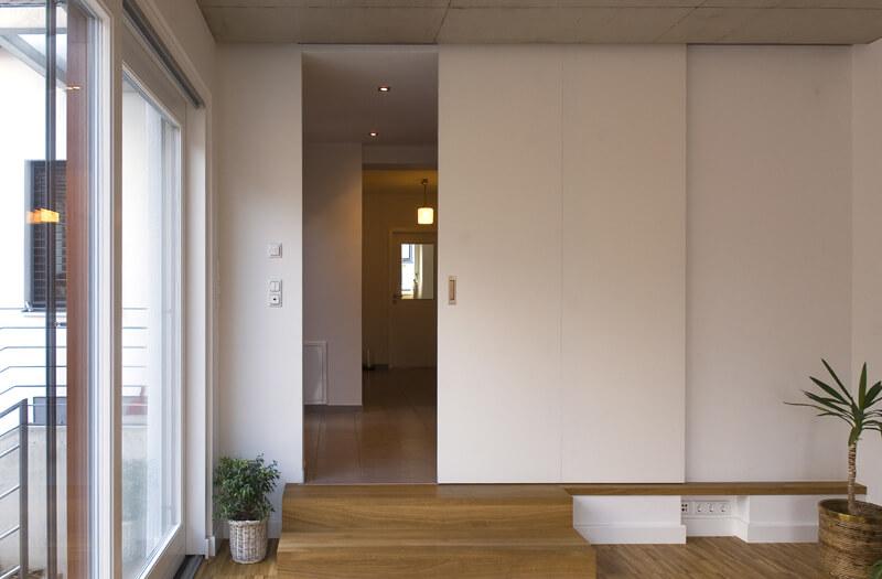 Rahmenlose weiße Schiebetüre als Raumteiler und Durchgangstüre