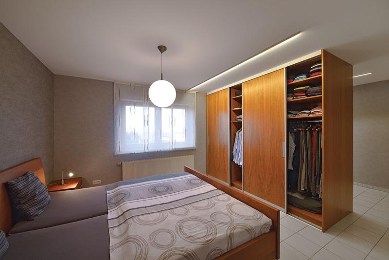 Schrank mit Schiebetüren als Raumteiler im Schlafzimmer, von beiden Seiten zu bedienen.